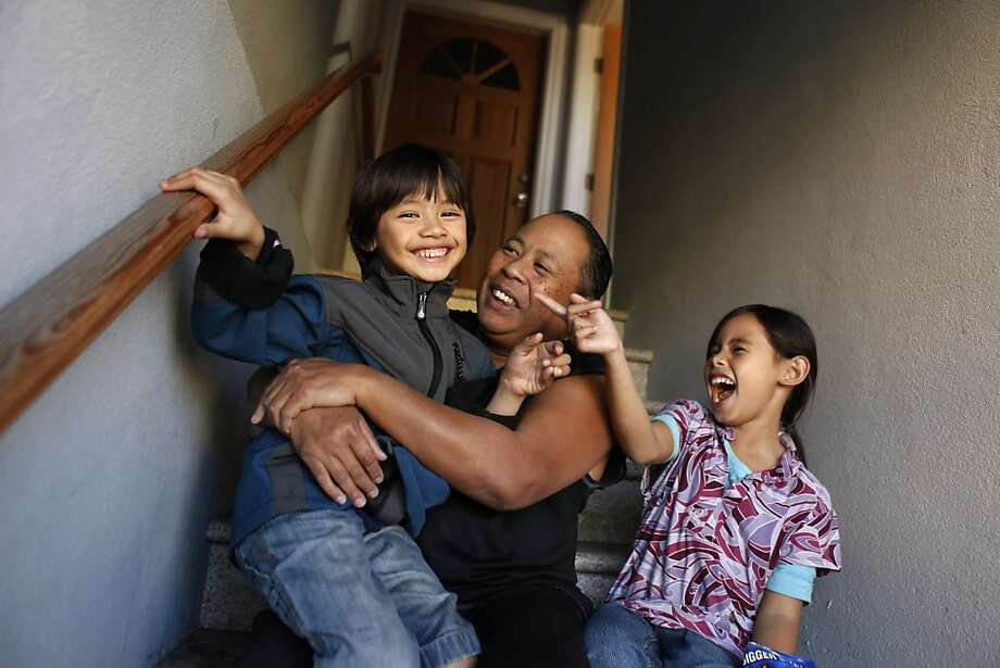 In this 2012 photo, Arthur Caberto, center, sits outside his San Francisco apartment with his kids, Anthony and Gemma. Caberto was able to get beds for his children through the Chronicle's Season of Sharing Fund. Photo: Carlos Avila Gonzalez, The Chronicle