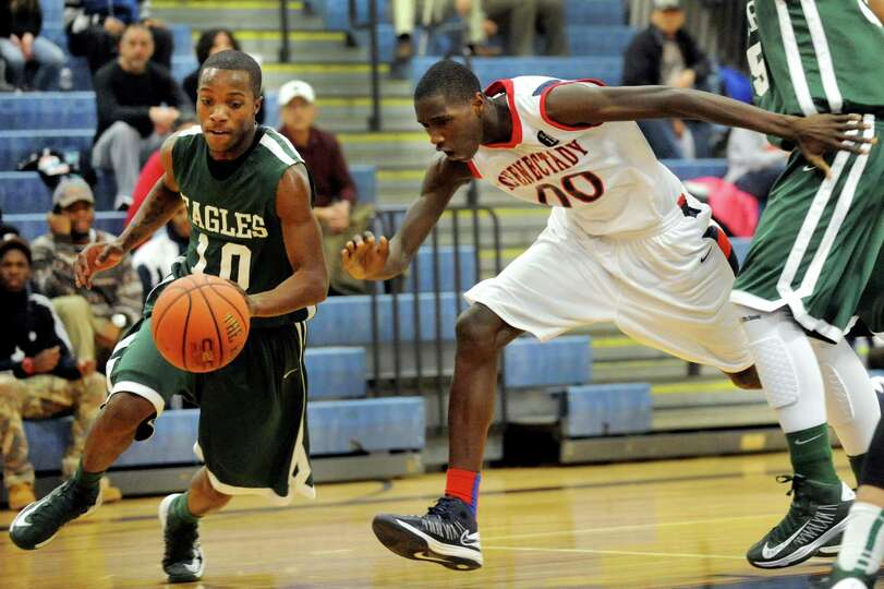 Green Tech's Maurice West (10), left, drives to the paint as Schenectady's Darius Macon (00) defends