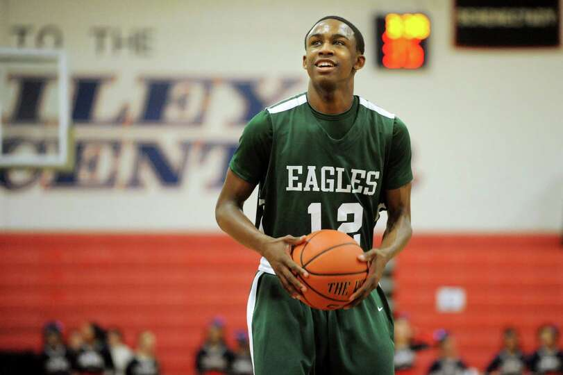 Green Tech's Jamil Hood Jr. (12) grins before shooting a free throw during their basketball game aga