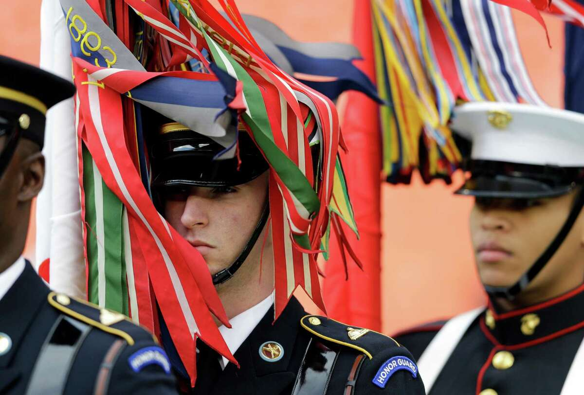Campaign ribbons blow onto members of the Honor Guard before they take the field with the Colors for events before the Military Bowl NCAA college football game between San Jose State and Bowling Green at RFK Stadium, Thursday, Dec. 27, 2012, in Washington. (AP Photo/Alex Brandon)