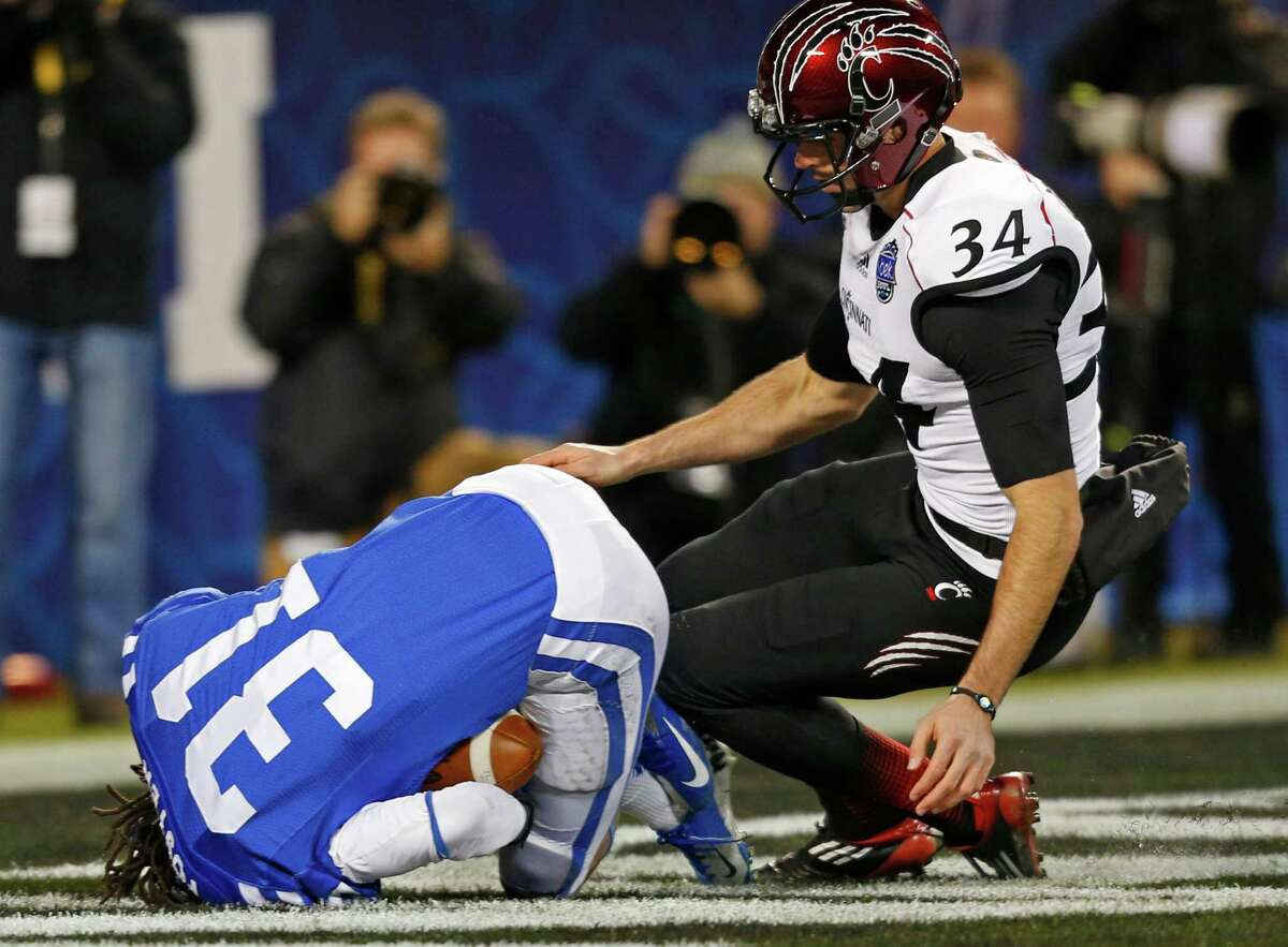 Duke's Tony Foster (31) recovers a blocked punt in the end zone for a touchdown as Cincinnati's Pat O'Donnell (34) looks on during the first half of the NCAA college football Belk Bow in Charlotte, N.C., Thursday, Dec. 27, 2012. (AP Photo/Chuck Burton)