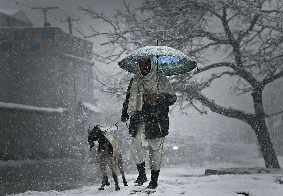 An Afghan man walks with his goat in Kabul, Afghanistan, Thursday, Dec. 27, 2012. Temperatures dropped to 1 degrees Celsius (34 Fahrenheit) in Kabul.  Photo: Ahmad Jamshid, Associated Press