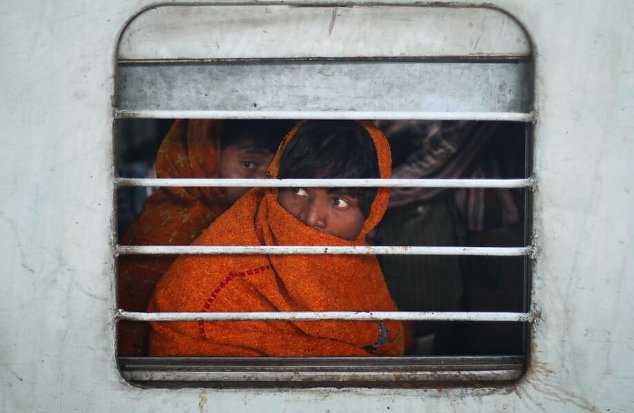 Indian passengers look out through the window of a train that arrived 16 hours after its scheduled arrival time in Allahabad, India, Thursday, Dec. 27, 2012. Severe fog in northern India brought down visibility, causing air, rail and road traffic delays.  Photo: Rajesh Kumar Singh, Associated Press