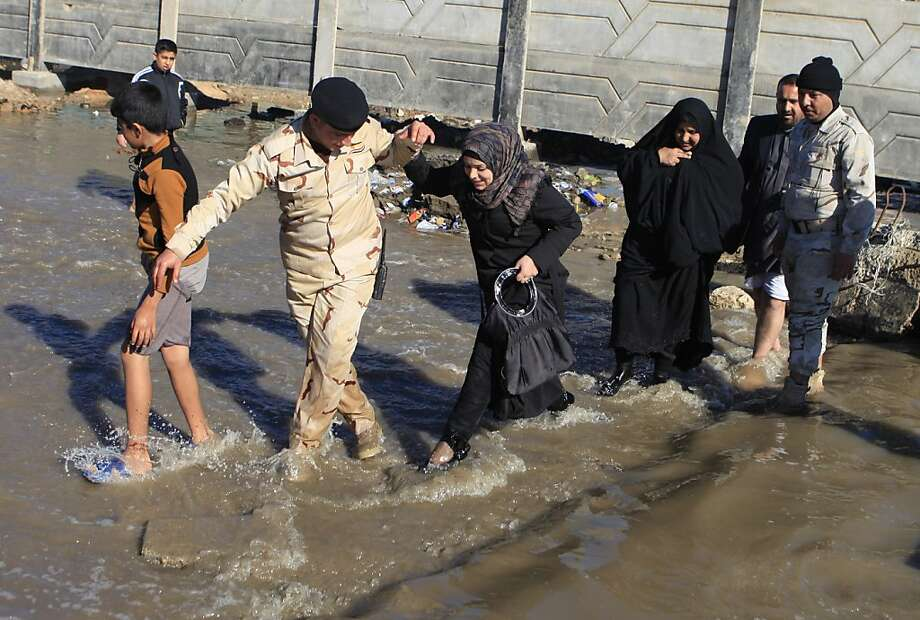 Iraqis make their way through flooded streets in Baghdad, Iraq, Thursday, Dec. 27, 2012. An unusually heavy rainstorm has collapsed shoddy houses in Iraq, killing several people, police and health officials said Wednesday.  Photo: Karim Kadim, Associated Press
