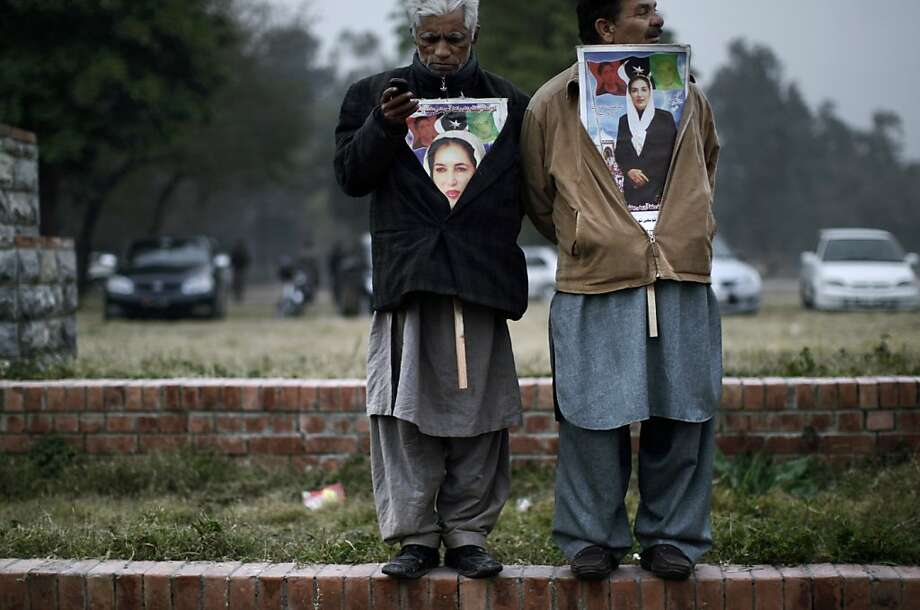 Supporters of Pakistan's slain leader Benazir Bhutto, one listens to speeches, right,  and the other checks his mobile phone, at a ceremony to mark the fifth anniversary of her death, in Islamabad, Pakistan, Thursday, Dec. 27, 2012. The 24-year-old son of former Pakistani Prime Minister Benazir Bhutto has launched his political career with a fiery speech on the fifth anniversary of his mother's assassination.  Photo: Muhammed Muheisen, Associated Press
