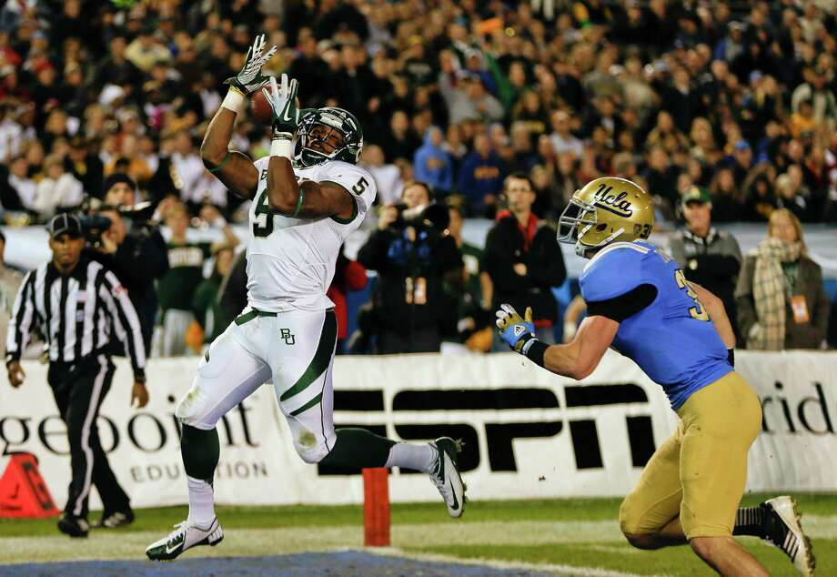 Baylor's Antwan Goodley hauls in an 8-yard touchdown pass from Nick Florence after beating UCLA linebacker Jordan Zumwalt, right, for the Bears' second touchdown in Thursday night's Holiday Bowl. For a recap of the game, visit chron.com/sports or the Chronicle's iPad app. Photo: Lenny Ignelzi, STF / AP