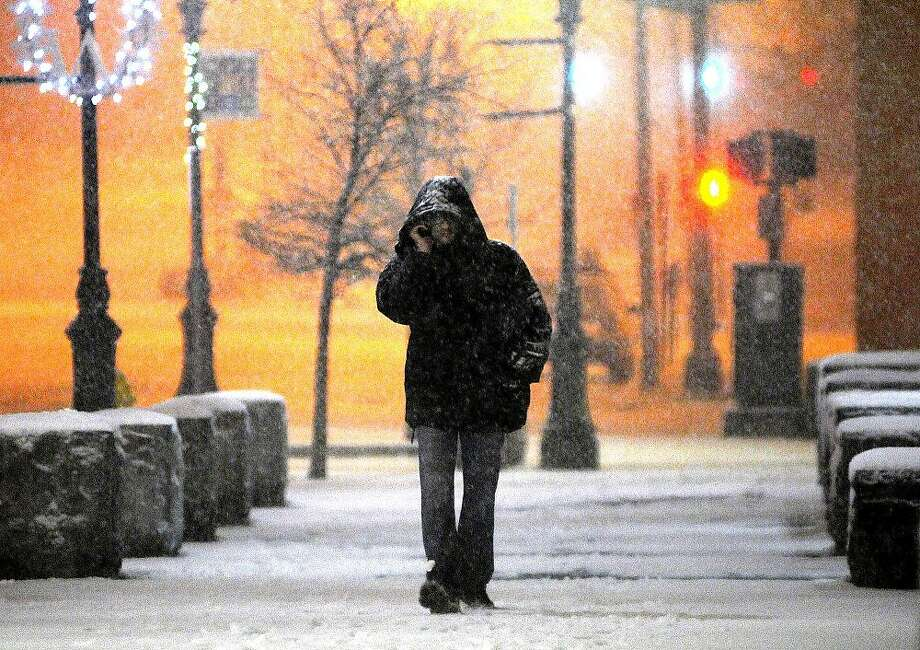 In this Wednesday, Dec. 26, 2012 photo, a man talks on his cellphone, as he walks along Main Street during a snowstorm late Wednesday night.  The winter storm brought snow to inland parts of the Northeast and driving rain and wind to areas along the coast Thursday, a day after it swept through the nation's middle, dumping a record snowfall in Arkansas and wrecking post-holiday plans for thousands of travelers. Photo: Steve Lanava, Associated Press