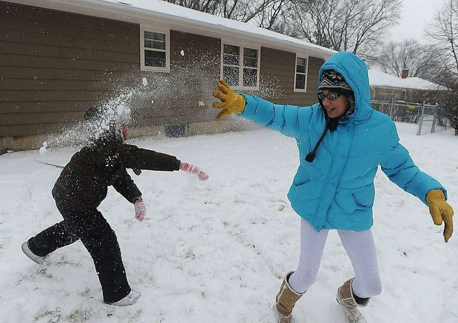 Devyn Dearring, 9, left, throws snow at her sister, Dailee Dearring, 11, while playing in the yard on Thursday, Dec. 27, 2012 in Sioux Falls, S.D. Photo: Jay Pickthorn, Associated Press