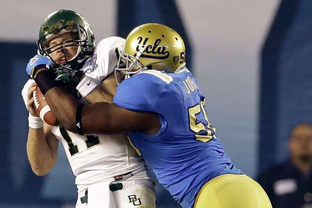 Baylor quarterback Nick Florence, left, is hit by UCLA defensive end Datone Jones after the play had been whistled dead on a third-and-28 play during the first half of the NCAA college football Holiday Bowl game on Thursday, Dec. 27, 2012, in San Diego. UCLA was called for the personal foul and a first down was awarded to Baylor. (AP Photo/Lenny Ignelzi) Photo: Lenny Ignelzi, Associated Press / AP