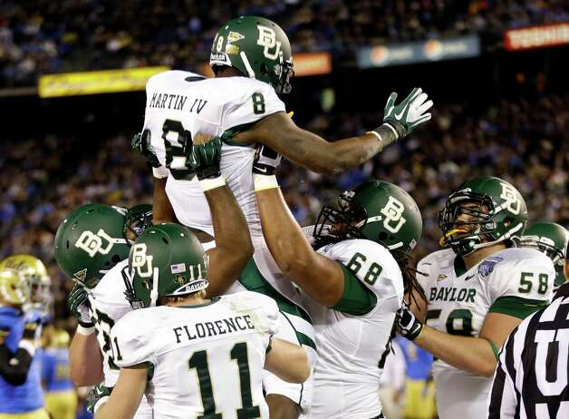 Baylor running back Glasco Martin is lifted by teammates after scoring a touchdown against UCLA during the first half of the NCAA college football Holiday Bowl game, Thursday Dec. 27, 2012, in San Diego. (AP Photo/Lenny Ignelzi) Photo: Lenny Ignelzi, Associated Press / AP