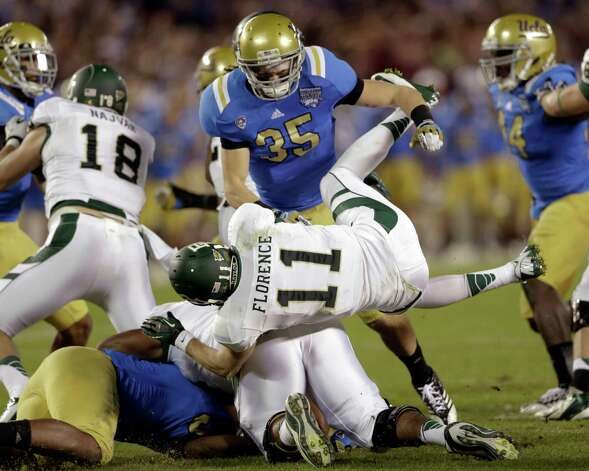 Baylor quarterback Nick Florence (11) is sent flying after being hit by UCLA linebacker Jordan Zumwalt while throwing a 48-yard completion during the first half of the NCAA college football Holiday Bowl game on Thursday, Dec. 27, 2012, in San Diego. (AP Photo/Lenny Ignelzi) Photo: Lenny Ignelzi, Associated Press / AP