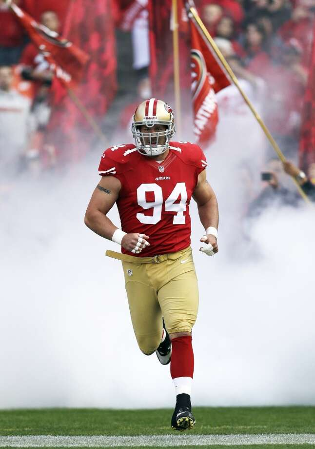 In this Sept. 16, 2012, file photo, San Francisco 49ers defensive end Justin Smith runs onto the field at the start of an NFL football game against the Detroit Lions in San Francisco. Smith has started 185 consecutive starts for the 49ers and should play against Seattle despite a left elbow injury. The 49ers are in the playoffs, and a win gives them the NFC West title.