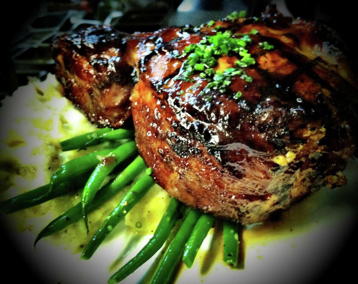 A house-smoked double-thick pork chop, cheddar mashed potatoes, fresh haricots vert and blueberry-bourbon barbecue sauce. (Cella Bistro)