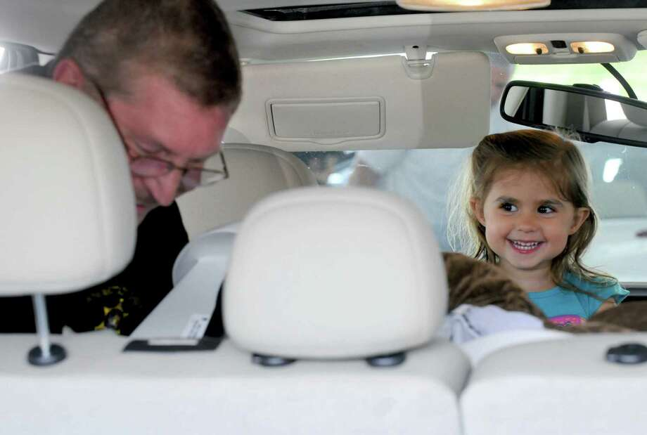 Three-year-old Ava Bachta of Troy watches as Schenectady Sheriff Deputy David Leffingwell installs her car seat during the Albany County 15th annual child safety seat check at Colonie Center in Colonie N.Y. Friday June 8, 2012. (Michael P. Farrell/Times Union) Photo: Michael P. Farrell, Albany Times Union / 00017971A