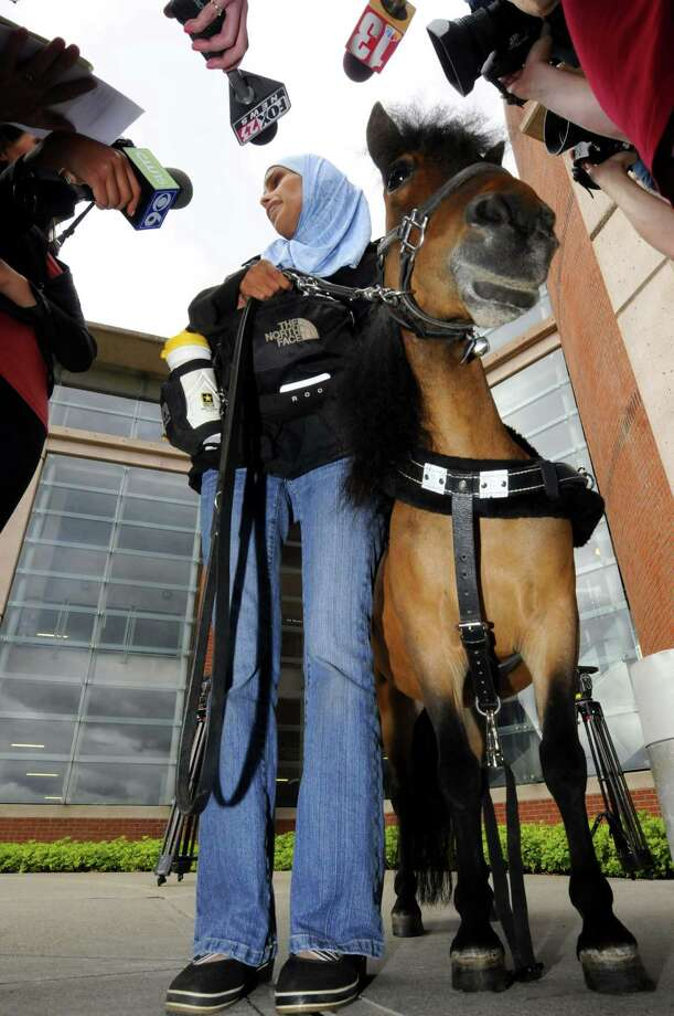 Mona Ramouni, who is blind, talks with local media following her arrival at Albany International Airport with Cali her guide horse in Colonie N.Y. Tuesday June 26, 2012. (Michael P. Farrell/Times Union) Photo: Michael P. Farrell, Albany Times Union / 00018237B