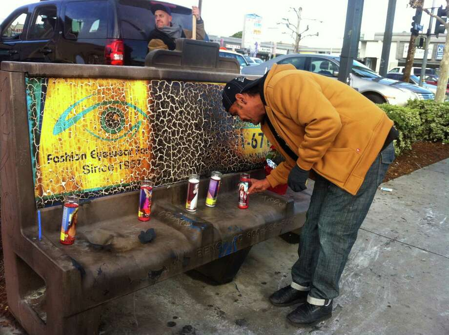 Phil Furtado places candles on a burned city bus bench in Los Angeles on Thursday Dec. 27,2012. Police arrested a man for allegedly setting a 67-year-old woman on fire who was sleeping on the bus stop bench.  A witness said he saw a man come out of the store and pour something on the woman who had been sleeping on a bench before striking a match and setting her ablaze. The woman, who may be homeless, was taken to a hospital and listed in critical condition. (AP Photo/Greg Risling) Photo: Greg Risling, STF / AP
