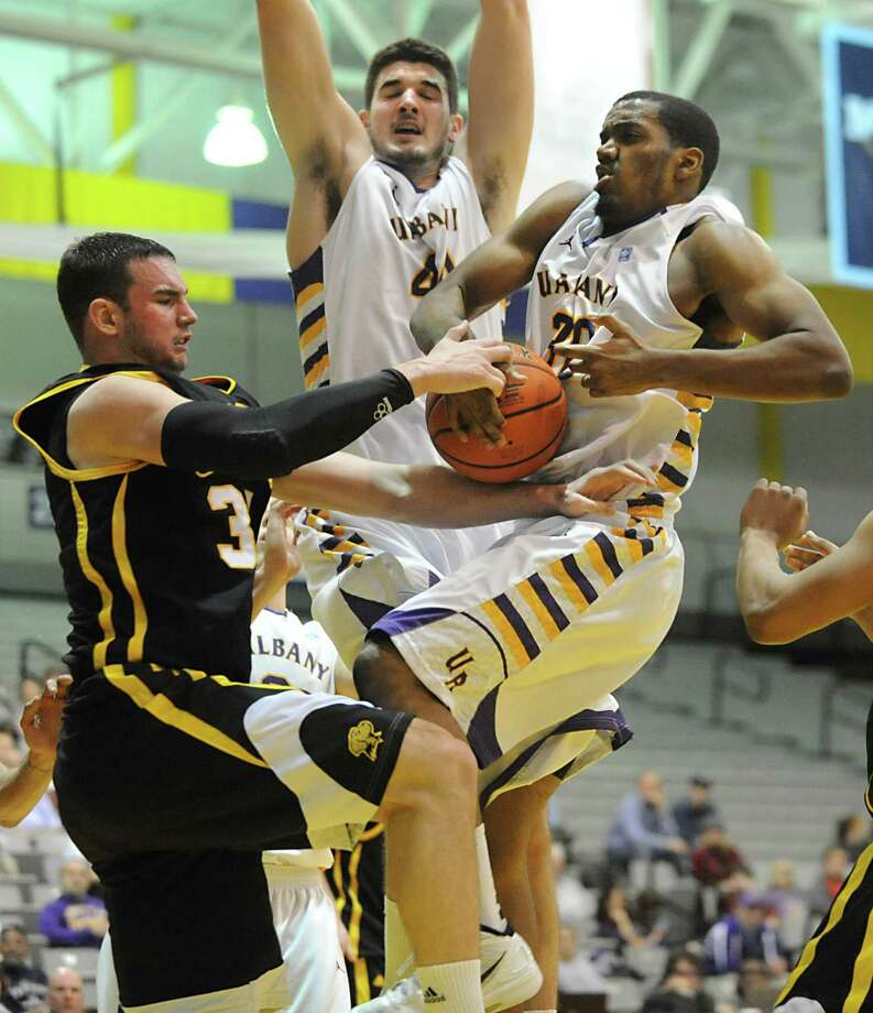 UAlbany's John Puk, center, and Jayson Guerrier try to come down with a rebound against UMBC's Jake Wasco during a basketball game at the SEFCU Arena on Wednesday, Feb. 1, 2012 in Albany, N.Y.  (Lori Van Buren / Times Union) Photo: Lori Van Buren, Albany Times Union / 00016255A