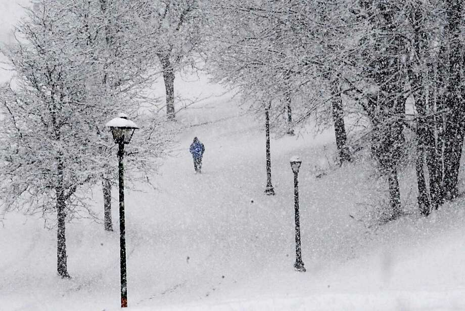 A pedestrian walks down a path in Lincoln Park   during a snowstorm Wednesday, Feb. 29, 2012 in Albany, N.Y. The Capital Region finally has received a significant snowfall. (Lori Van Buren / Times Union) Photo: Lori Van Buren, Albany Times Union / 00016618A