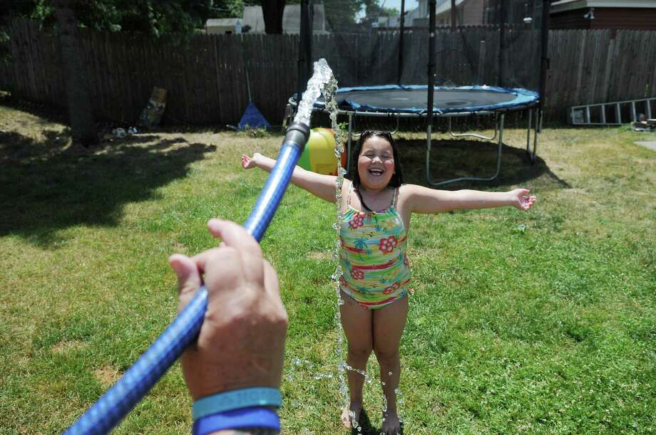 Mattia, 8, gets cooled off as her great aunt Leslie Heermance sprays her down with a hose  on Tuesday, July 3, 2012 in Rotterdam, NY.  Heermance said she was unaware of the town's water conservation measure that was in place.  (Paul Buckowski / Times Union) Photo: Paul Buckowski, Albany Times Union / 00018338A