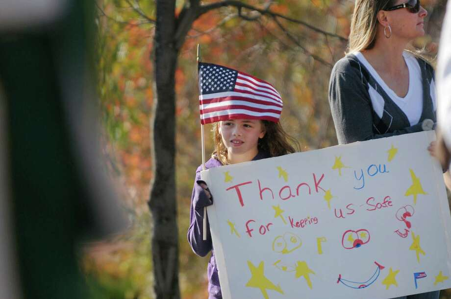 Josie O'Hare, 9, and her mom, Deana O'Hare from Westerlo hold a sign that Josie made as they watch the Albany Veterans Day Parade on Monday, Nov. 12, 2012 in Albany, NY.  Deana said that she and her three daughters come to the parade every year rain or shine to show their appreciation for the veterans and the active duty soldiers.   (Paul Buckowski / Times Union) Photo: Paul Buckowski, Albany Times Union / 00020041A