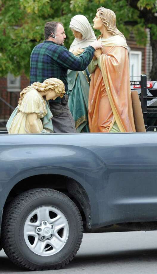 Restoration Artist Artur Matia holds on to religious sculptures that were removed from a church at 369 Livingston Ave. in Albany, to make way for the Sister Maureen Joyce Soup Kitchen, Oct. 19, 2011. Matia was tasked with restoring the religious sculptures while the church was being renovated. Eventually, the sculptures will be returned to the renovated site. (Skip Dickstein/Times Union) Photo: ALL