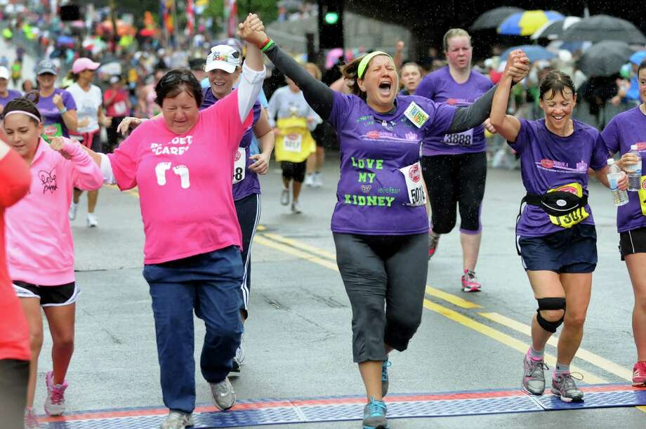 "Kidney recipient Gina Picarillo, center, celebrates as she crosses the finish line with Debbie Griner, left, and Jean Colaneri during the Freihofer's Run for Women on Saturday, June 2, 2012, in Albany, N.Y. ""I did this for my donor,"" Picarillo said of the race. (Cindy Schultz / Times Union) Photo: Cindy Schultz, Albany Times Union / 00017846B"