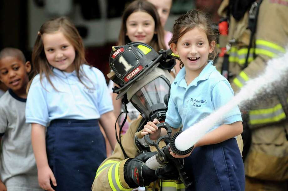 Kendall LaFore, 8, of St. Augustine's School, right, holds the nozzle as she helps firefighter Frank Razzano shoot water from a hose during a tour on Tuesday, June 12, 2012, at the Troy Fire Department in Troy, N.Y. Kendall and 17 other Troy City school students received awards for their fire prevention posters, an annual competition put on by the Troy Fire Department and the Uniformed Firefighters Association. (Cindy Schultz / Times Union) Photo: Cindy Schultz, Albany Times Union / 00018043A