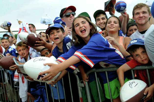 Julia Blackin, 10, of Arlington, Va., center, hollers for autographs  at the end of Giants Camp on Saturday, Aug. 4, 2012, at UAlbany in Albany, N.Y. Joining Julia are her brothers Daniel, 9, left, and Matthew, 4, right. (Cindy Schultz / Times Union) Photo: Cindy Schultz, Albany Times Union / 00018641A