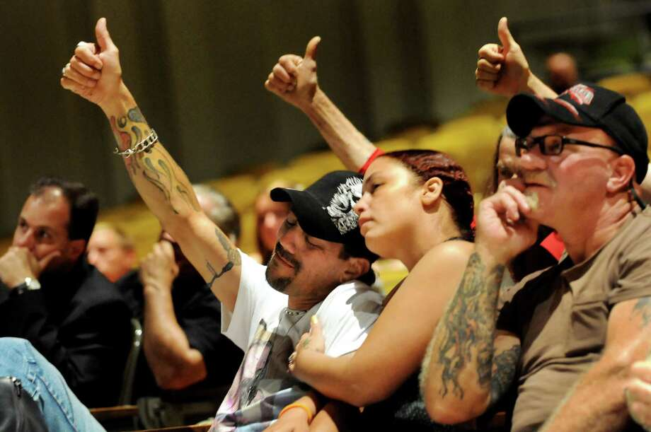 Shawn Zielinski, center, joins friends and family with a thumbs up during a memorial service for his son, Tylar, on Thursday, July 12, 2012, at Fonda Fultonville High School in Fonda, N.Y. Tylar, who's was known for giving the thumbs up sign, died at the age of 20 from Duchenne muscular dystrophy three weeks after graduating from high school. Shawn's fiance, Michelle Kaiser-Cade, sits next to him and shows her support. (Cindy Schultz / Times Union) Photo: Cindy Schultz, Albany Times Union / 00018413A