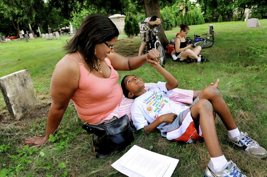 Margo Dickson of Schenectady and her son, David, 8, relax in the grass during the opening ceremony of the 12th Annual Capital District Juneteenth Celebration on Friday, June 15, 2012, at Vale Cemetery in Schenectady, N.Y. (Cindy Schultz / Times Union) Photo: Cindy Schultz, Albany Times Union / 00018057A