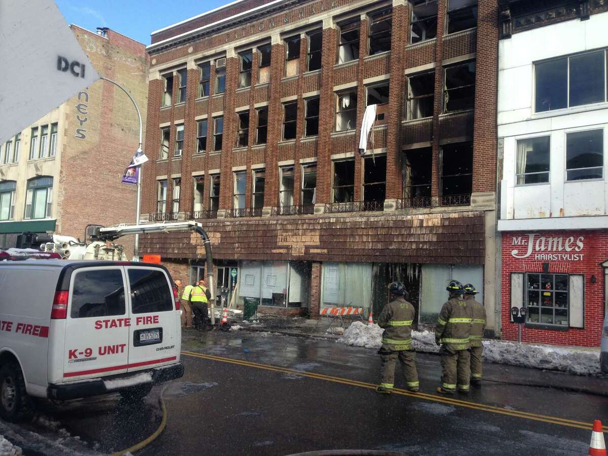 Firefighters survey the scene after a fire at 237-247 State St., Schenectady, gutted the apartment building and forced the city to temporarily close a stretch of the downtown street. (PAUL NELSON / TIMES UNION)