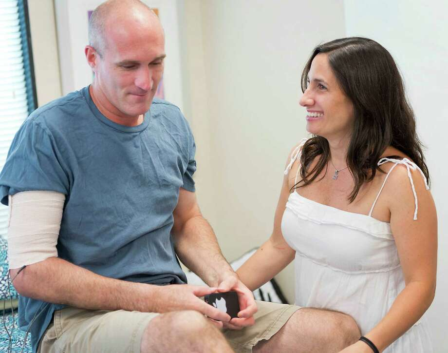 Stamford Police officer Troy Strauser and his wife Torey Strauser during a break in a therapy session Troy was having at Coastal Hand Therapy in Nowralk, CT on Monday July 2nd, 2012. Officer Strauser was injured while chasing a robbery suspect this past May. Photo: Mark Conrad / Stamford Advocate Freelance