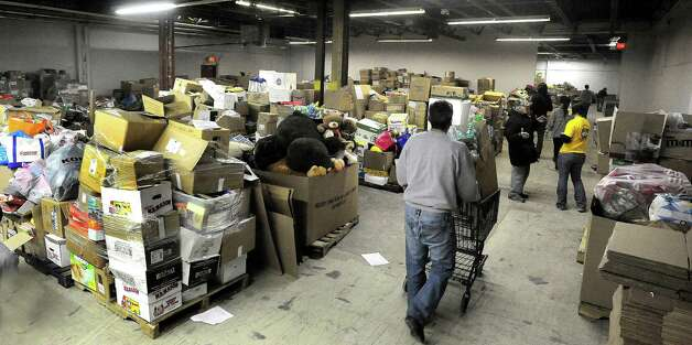 Volunteers struggle to keep up with the quantity of donated stuffed goods in a Simms Lane warehouse in Newtown Thursday, Dec. 27, 2012. Photo: Michael Duffy