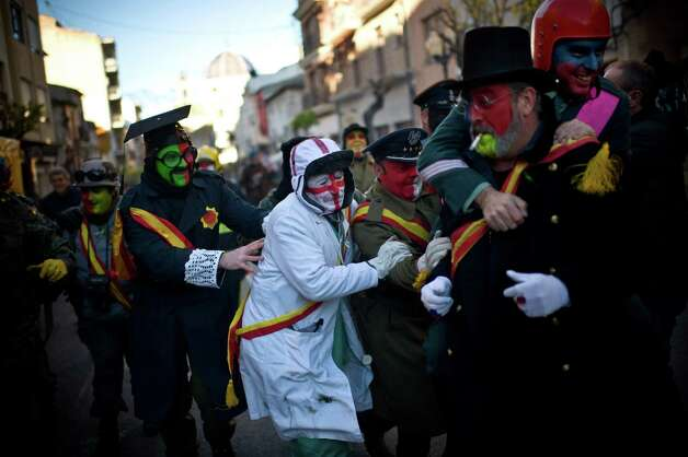 Revelers in fancy dress walk toward the battle of Enfarinats, a flour fight in celebration of the Els Enfarinats festival on Friday in Ibi, Spain. Citizens of Ibi annually celebrate the festival with a battle using flour, eggs and firecrackers. The battle takes place between two groups, a group of married men called 'Els Enfarinats' which take the control of the village for one day pronouncing a whole of ridiculous laws and fining the citizens that infringe them and a group called 'La Oposicio' which try to restore order. At the end of the day the money collected from the fines is donated to charitable causes in the village. The festival has been celebrated since 1981 after the town of Ibi recovered the tradition but the origins remain unknown.  (Photo by David Ramos/Getty Images) Photo: David Ramos, Ap/getty / 2012 Getty Images
