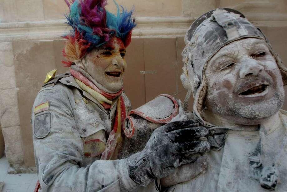 Nothing makes a man or woman smile like a flour bomb. (AP Photo/Alberto Saiz) Photo: Ap/getty