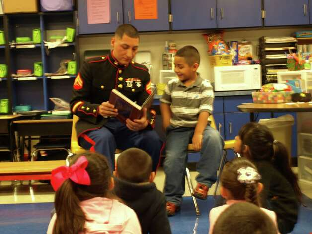 "Corporal Salvador Gonzales reads ""The Night Before Christmas to his son, Nathaniel, after returning from duty in Japan. Photo: Express-News"