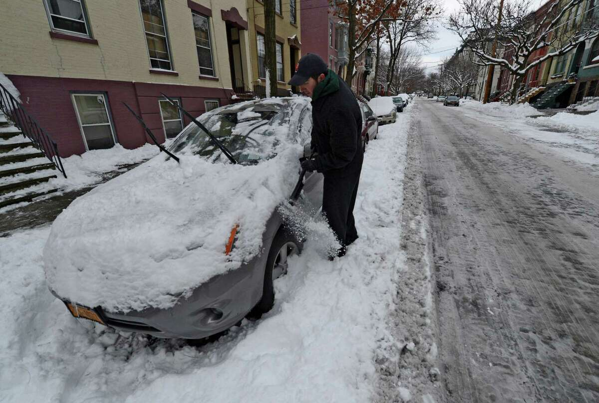 Kevin Bronner cleans a friend's car before moving it to the correct side for the snow emergency in Albany, N.Y., on Dec 28, 2012. (Skip Dickstein/Times Union)