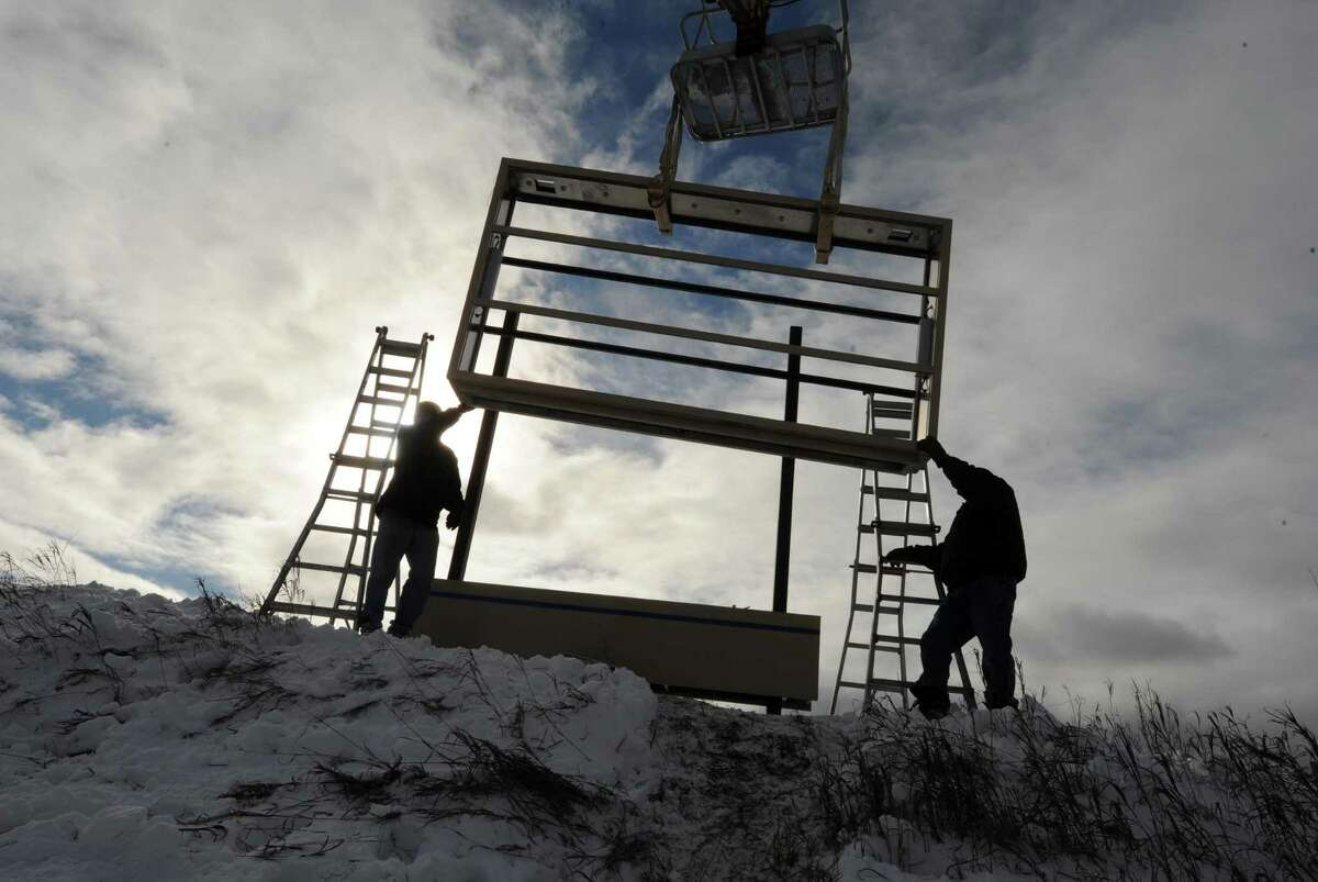 Workers from AJ Signs make their way through the snow while installing a new sign for the Airline Corporate Park in Colonie, N.Y., Friday Dec. 28, 2012. (Michael P. Farrell/Times Union)