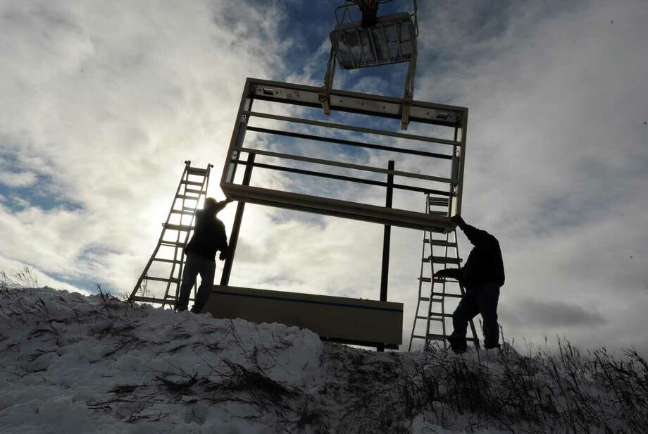 Workers from AJ Signs make their way through the snow while installing a new sign for the Airline Corporate Park in Colonie, N.Y., Friday Dec. 28, 2012. (Michael P. Farrell/Times Union) Photo: Michael P. Farrell