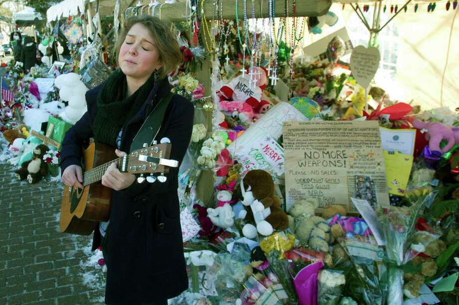 Courtney Preis, of Newtown, plays a guitar and sings a song dedicated to the memory of the victims of the Sandy Hook school shooting Friday, Dec. 28, 2012, in Newtown. Handmade items made from a variety of mediums dot the landscape of the many makeshift memorials for the 26 victims of the Sandy Hook Elementary school shooting. Photo: Brett Coomer, Brett Coomer/Hearst Newspapers / The News-Times