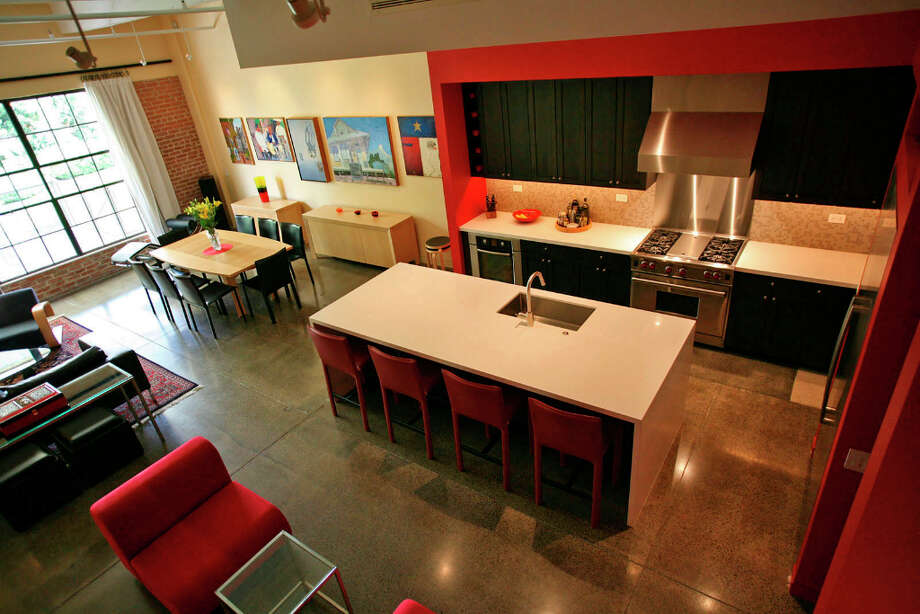 Julius and Kathy Gribou focused on the color red in their kitchen at the Camp Street Lofts. On the first floor, the kitchen gets one corner of the open area while the rest of the room contains a dining table with seating for eight, a sofa and two chairs arranged around a glass table and a pair of red chairs in a casual area. Photo: Danny Warner, For The Express-News / San Antonio Express-News
