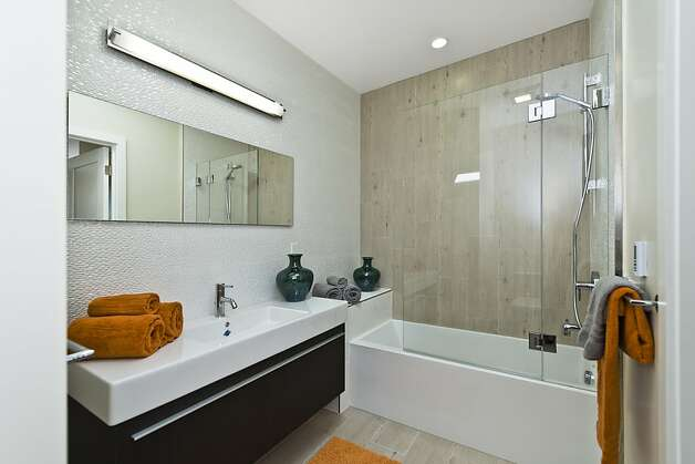 Porcelanosa tiled walls and Mirabelle soaking tub are featured in the bathroom. Photo: Vanguard Properties/SF