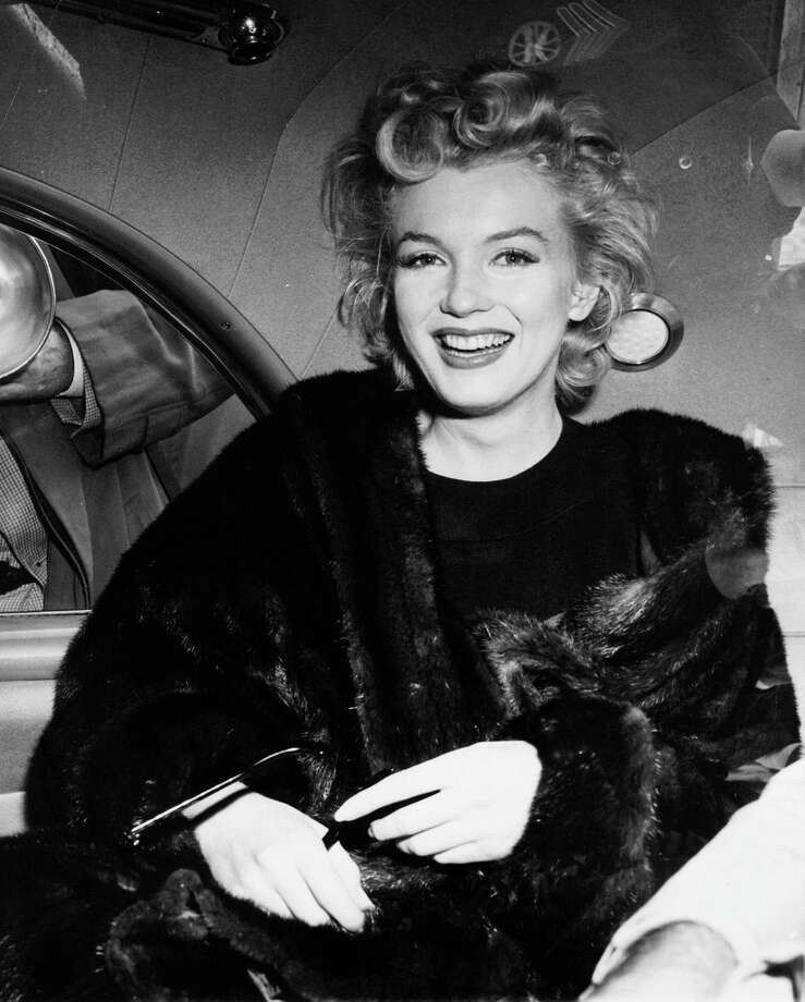 FILE - In this June 2, unknown year, file photo, actress Marilyn Monroe smiles in a car after arriving tousled from an all-night plane flight from Hollywood to Idlewild Airport, in New York. The actress said she planned to rest in New York before going to England to make a new movie with Sir Laurence Olivier. In late 2012, the FBI has released a new version of files it kept on Monroe that reveal the names of some of her acquaintances who had drawn concern from government officials and members of her entourage over their suspected ties to communism. (AP Photo, File) Photo: Uncredited