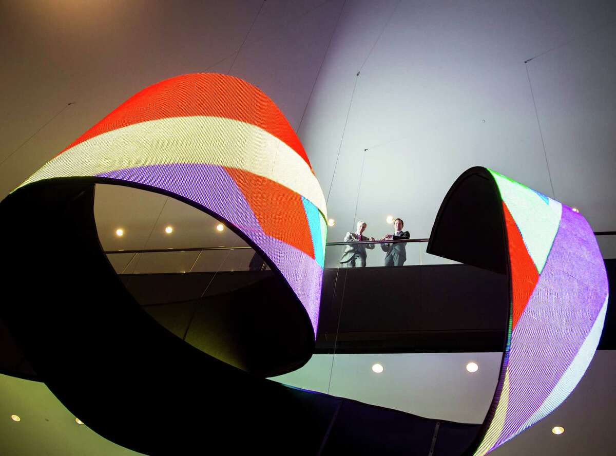 """CBRE executives Chuck Moore, left, and Cody Armbrister stand above the art installation """"Waves"""" at Two Houston Center created by Spanish artist Daniel Canogar, Thursday, Dec. 13, 2012, in Houston. The 100-foot-long ribbon-shaped LED video piece is suspended above the ceiling of the atrium. ( Michael Paulsen / Houston Chronicle )"""