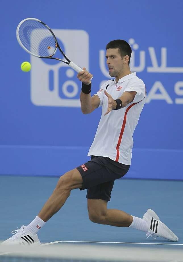 Novak Djokovic hits a return in his semifinal victory over David Ferrer at the exhibition tournament in Abu Dhabi. Photo: Kamran Jebreili, Associated Press