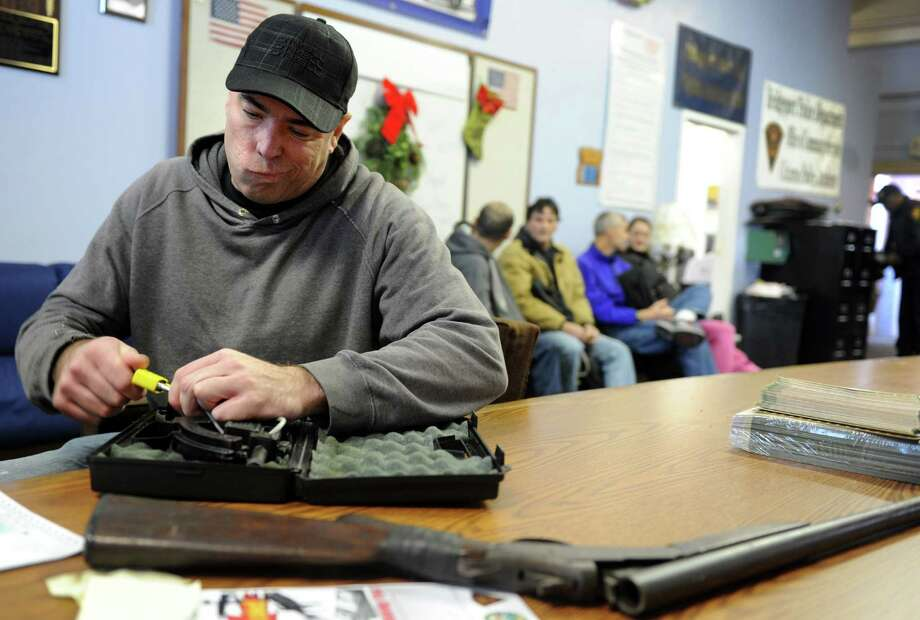 Chris Fumal, of New Milford, takes the lock off of his Intratec TEC-22 semi-automatic handgun as he turns it in during a gun buyback event at the Bridgeport Police Department's Community Services Division Friday, Dec. 28, 2012 in Bridgeport, Conn. In the wake of the tragedy in Newtown, Conn., the city raised $100,000 for the program and will offer up to $200 value for a working handgun, $75 for rifles and higher amounts for assault-type rifles.  The buy back will continue every Saturday until the city gives out all of the funds which includes an additional $10,000 in gift cards from the Food Bazaar grocery store. Photo: Autumn Driscoll / Connecticut Post