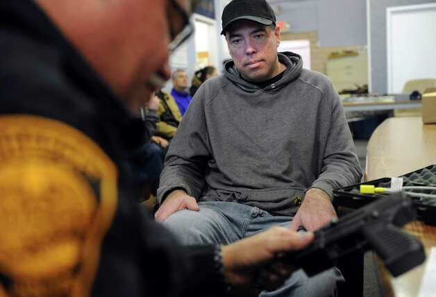 Chris Fumal, of New Milford, watches Officer Pete Garcia log his Intratec TEC-22 semi-automatic handgun during a gun buyback event at the Bridgeport Police Department's Community Services Division Friday, Dec. 28, 2012 in Bridgeport, Conn. In the wake of the tragedy in Newtown, Conn., the city raised $100,000 for the program and will offer up to $200 value for a working handgun, $75 for rifles and higher amounts for assault-type rifles.  The buy back will continue every Saturday until the city gives out all of the funds which includes an additional $10,000 in gift cards from the Food Bazaar grocery store. Photo: Autumn Driscoll / Connecticut Post