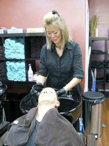 Inson Neglio, stylist and manager of Brookfield's SoHo Salon, washes HealthyLife cover model Patti Garland's hair after applying color. Photo: Rebecca Haynes / Healthy Life
