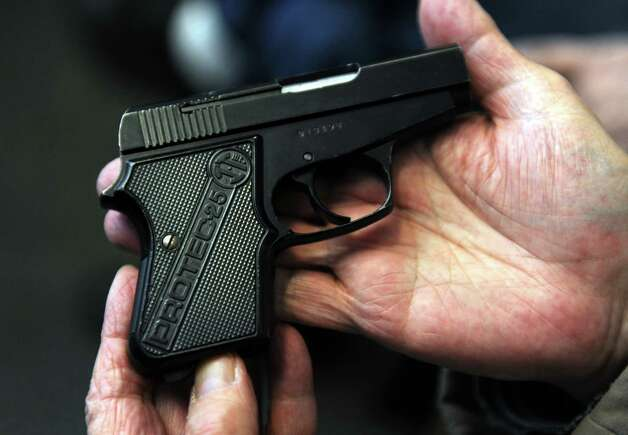A man waits to turn in an Intertec Protec-25 semi-Auto pistol during a gun buyback event at the Bridgeport Police Department's Community Services Division Friday, Dec. 28, 2012 in Bridgeport, Conn. In the wake of the tragedy in Newtown, Conn., the city raised $100,000 for the program and will offer up to $200 value for a working handgun, $75 for rifles and higher amounts for assault-type rifles.  The buy back will continue every Saturday until the city gives out all of the funds which includes an additional $10,000 in gift cards from the Food Bazaar grocery store. Photo: Autumn Driscoll / Connecticut Post