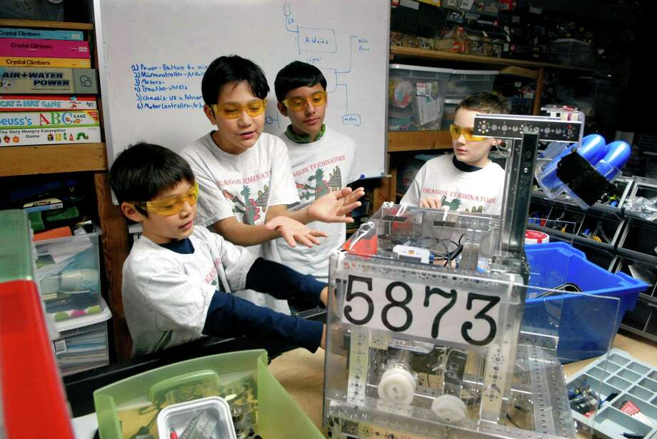 Artemis Shung (8) his brother Ajax (11), Gabriel Quiroga (11) and Christopher McDonnell (11) on Friday December 21, 2013 with the robot they built in Old Greenwich, Conn. Photo: Dru Nadler / Stamford Advocate Freelance